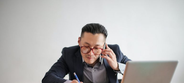 A person calling someone while working on their laptop
