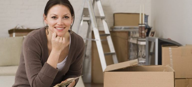 An image of a woman surrounded by moving boxes provided by our Tribeca movers
