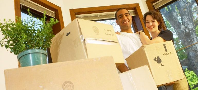 An image of a couple surrounded by moving boxes, happy with the Manhattan moving services they received.