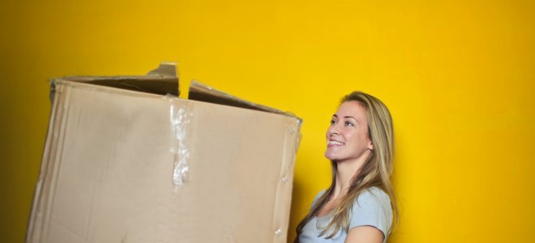 A woman carrying a moving box