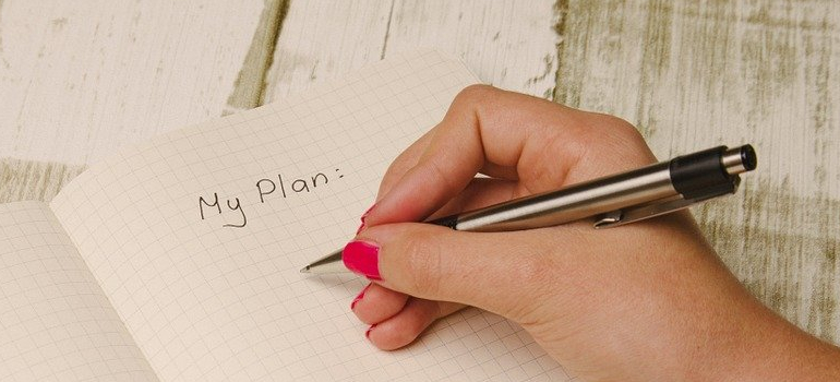 a hand writing a plan of Cutting costs on storage expenses