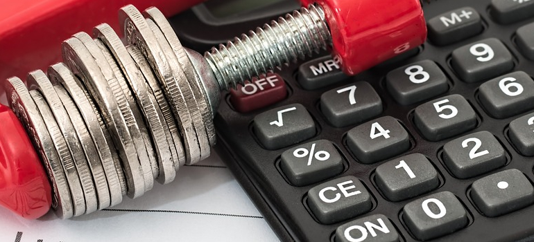 coins and calculator as a debt you need to clear before Buying your first home