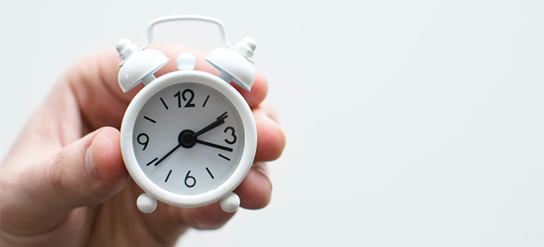 A hand holding a small alarm clock
